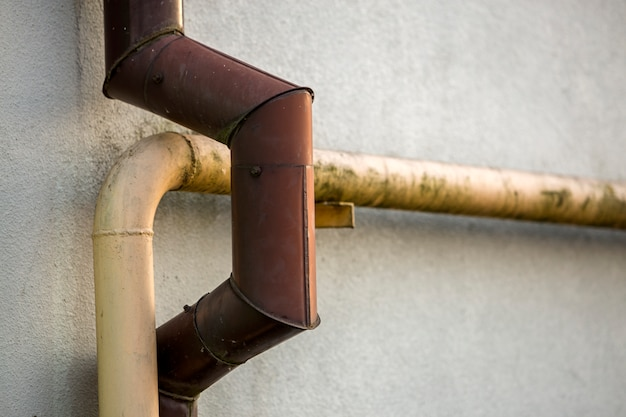 Close-up detail of old dirty painted yellow natural gas and brown gutter rain water pipes Premium Photo