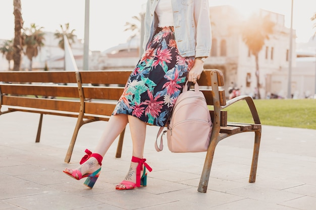 Close up details of legs in pink sandals of stylish woman walking in city street in printed colorful skirt, holding pink leather backpack, summer style footwear trend Free Photo