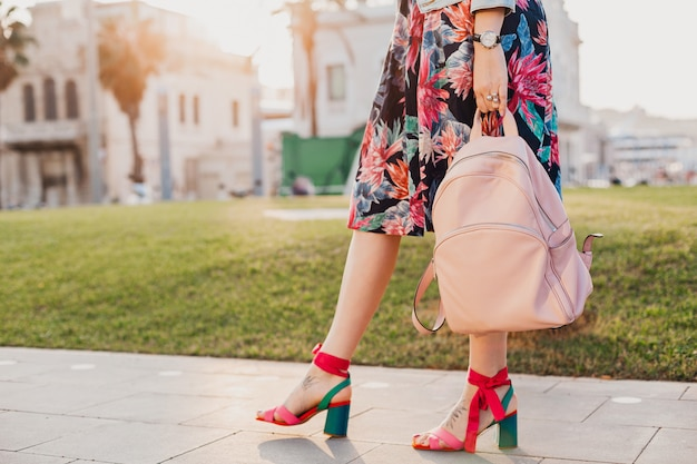 Close up details of legs in pink sandals of stylish woman walking in city street in printed colorful skirt, holding pink leather backpack Free Photo