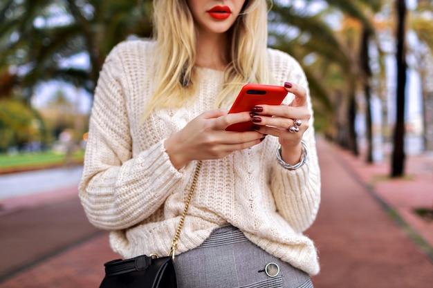 Закройте детали женщины, позирующей на улице, и нажмите на ее смартфон, красные губы и уютный модный белый свитер, мода. Бесплатные Фотографии