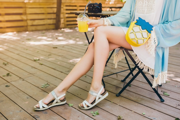 Close up details of young woman sitting in deck chair in summer fashion outfit Free Photo