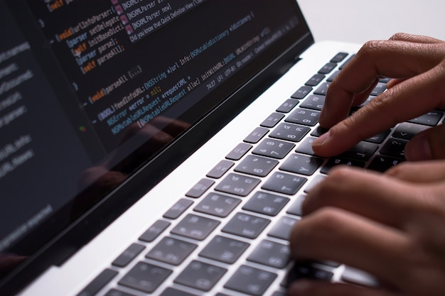 Close up. the developer's hand is creating code on a computer monitor on a white desk. Premium Photo