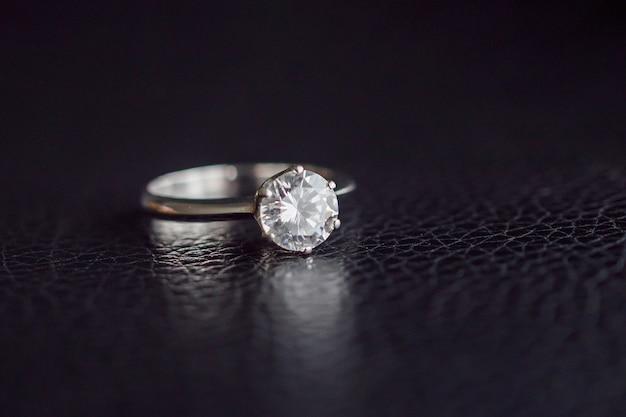 Крупным планом ювелирные изделия с бриллиантовым кольцом на черной кожаной поверхности Premium Фотографии