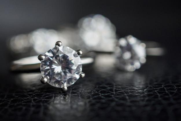 Крупным планом ювелирные изделия с бриллиантовыми кольцами на черной кожаной поверхности Premium Фотографии