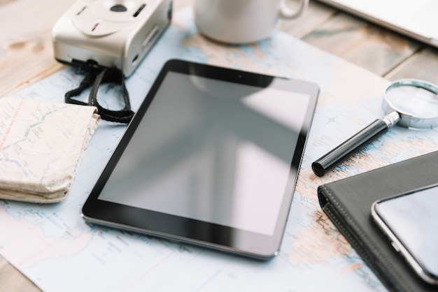Close-up of digital camera; digital tablet; magnifying glass and diary on map Free Photo