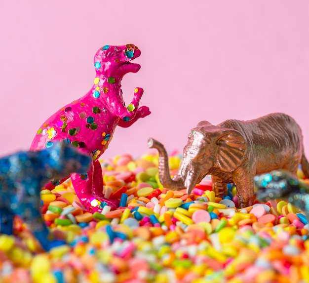 Close up of dinosaurs and animal figure toys on sweet candy sprinkles Free Photo