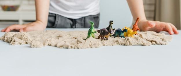 Dinosauri del primo piano sulla sabbia Foto Gratuite