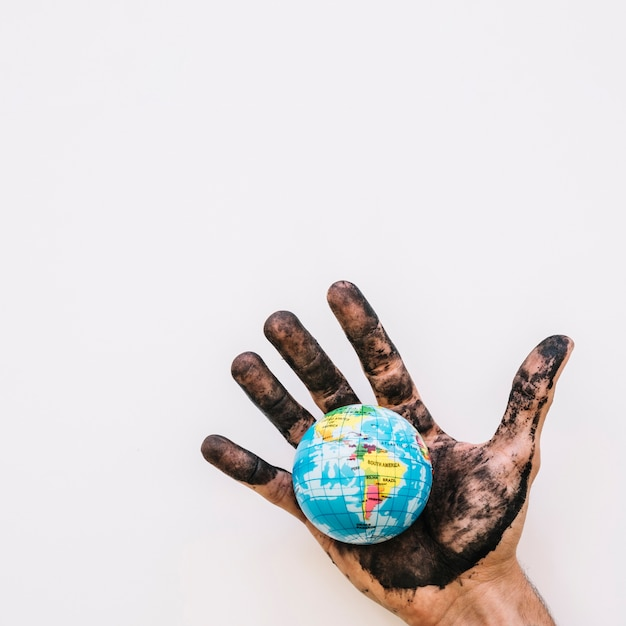 Close-up of dirty human hand with globe over white surface Free Photo