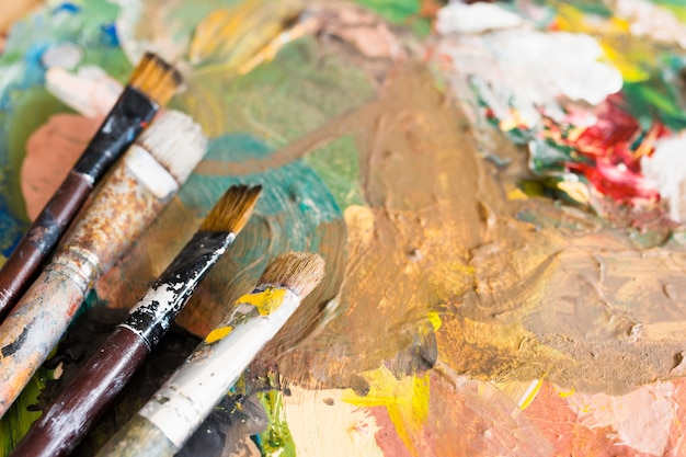 Close-up of dirty paintbrushes over oil painted surface Free Photo