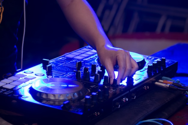 Close up of dj hands on stage mixing, disc jockey and mix tracks on sound mixer controller, playing music at bar, disco tech or night club party. Premium Photo