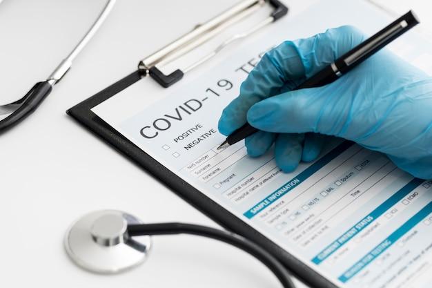Medico del primo piano che completa il modulo medico covid Foto Gratuite