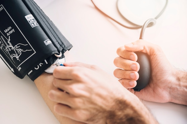 Close-up of a doctor's hand checking blood pressure of patient Free Photo