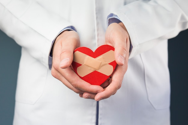 Close-up of doctor's hand holding red heart with crossed bandages Free Photo