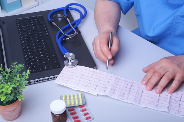 Close-up of doctor's handwriting prescription and holding bottle with pills. Premium Photo