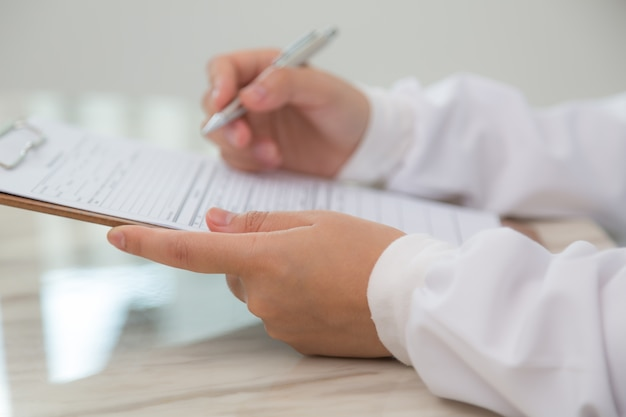Close-up of doctor using clipboard and pen Free Photo