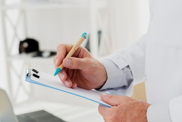 Close-up of doctor writing on clipboard Free Photo