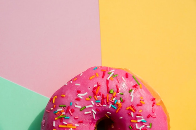 Close-up of donut with sprinkles against yellow; pink; and mint green backdrop Free Photo
