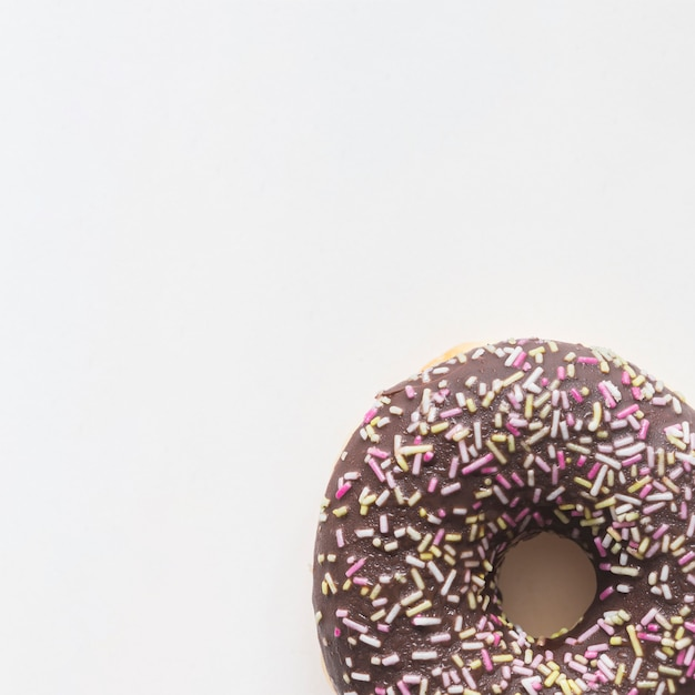 Close-up of donut with sprinkles on white background Free Photo