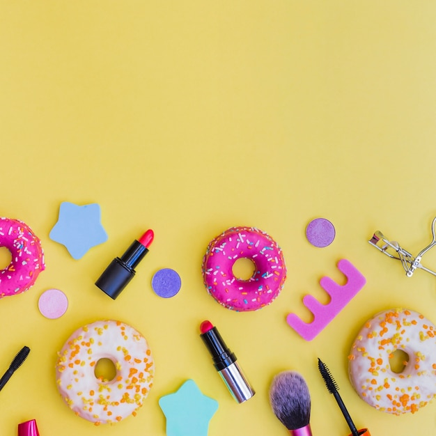 Close-up of donuts; lipstick; eyelash curler; makeup brush and toe divider on yellow background Free Photo