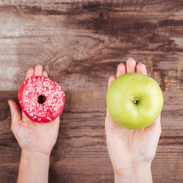 Close-up of doughnut and apple in palms Free Photo
