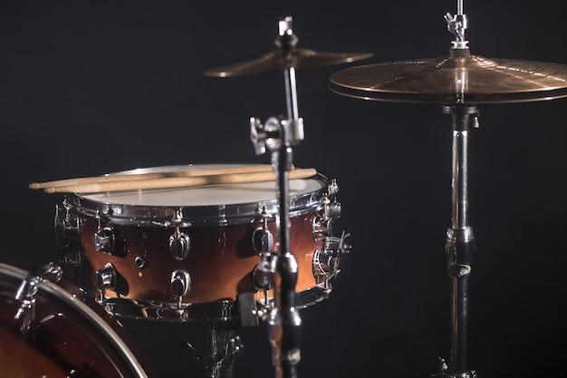 Макро барабан установлен в темной комнате на фоне прожектора. медные пластины на холодном фоне Бесплатные Фотографии