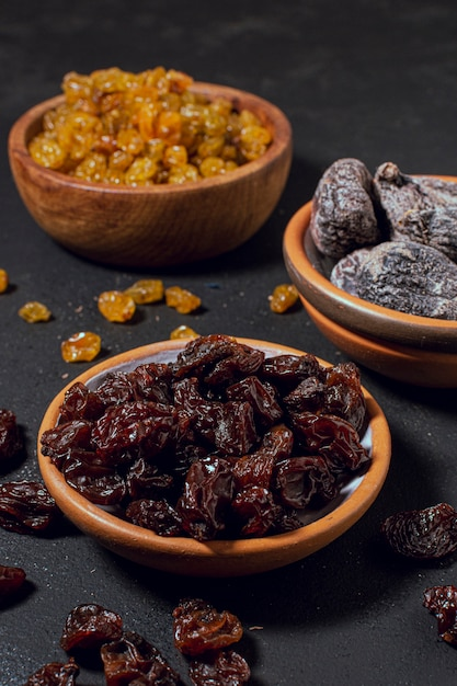 Close-up dry fruit and nuts in bowls Free Photo