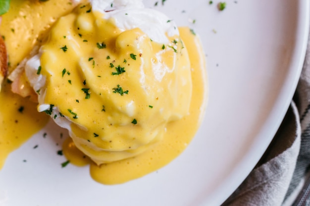Close up egg benedict served with salad in white plate on wooden table. Premium Photo