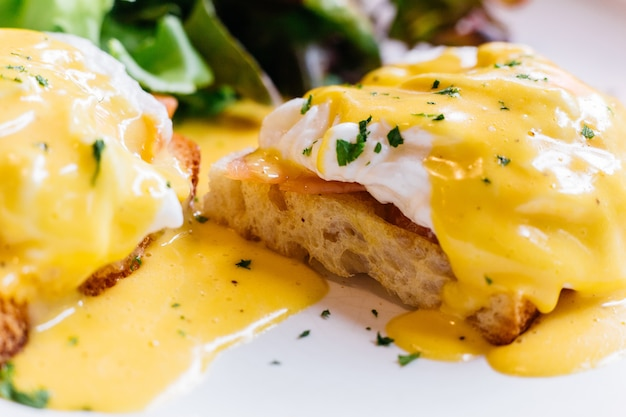 Close up egg benedict served with salad in white plate. Premium Photo