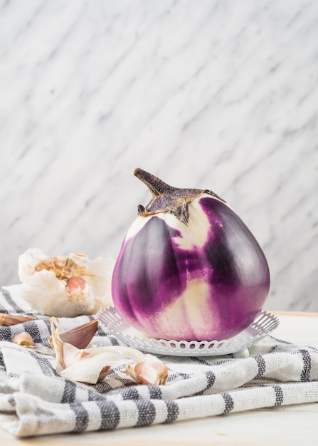Close-up of eggplant and garlic cloves on chequered pattern textile Free Photo