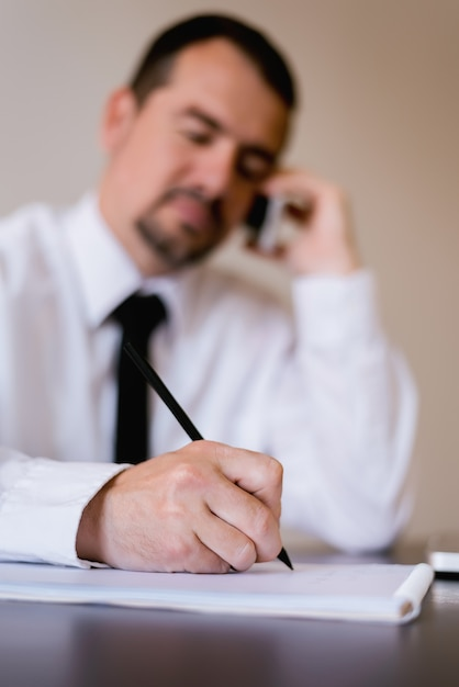 Close up of elder businessman signing contract or documents at his office Premium Photo
