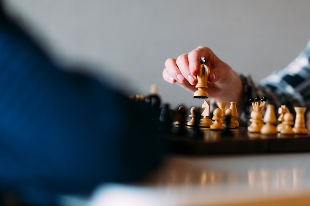 Close up elderly couple playing chess in retirement home Premium Photo