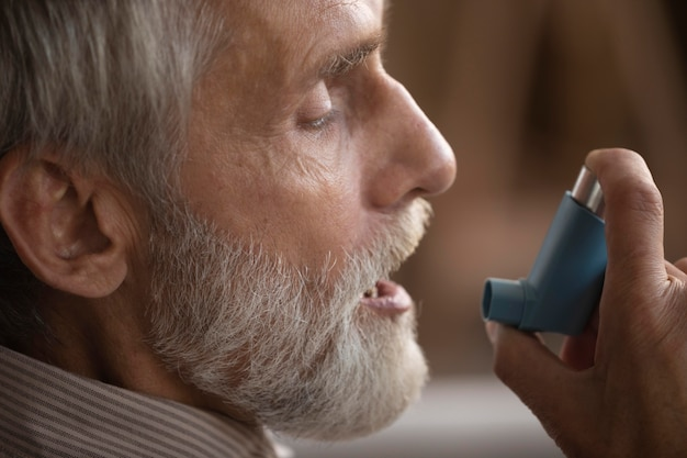 Close-up elderly man holding asthma inhaler Free Photo