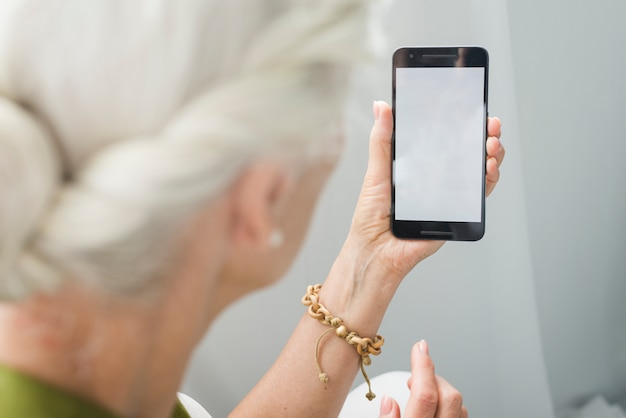 Close-up of elderly woman looking at smartphone with blank screen Free Photo