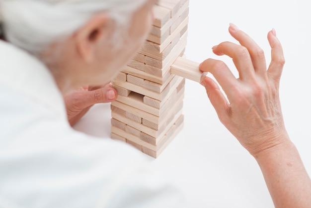 Close-up elderly woman playing jenga Free Photo