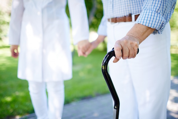 Close-up of elderly woman with walking stick Free Photo