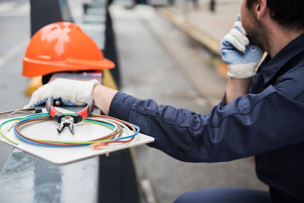 Close-up of electric equipment and electrician on street Free Photo