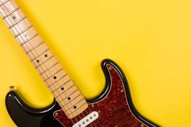 Close-up of electric guitar on yellow background, with copy space Premium Photo