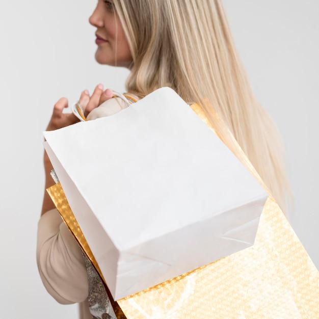 Sacchetti della spesa di trasporto della donna elegante del primo piano Foto Gratuite