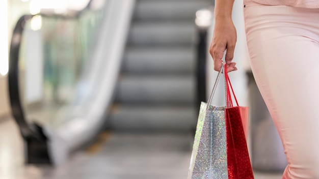 Close-up elegant woman carrying shopping bags Free Photo