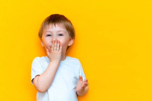Close up emotional surprised little boy covering mouth Premium Photo