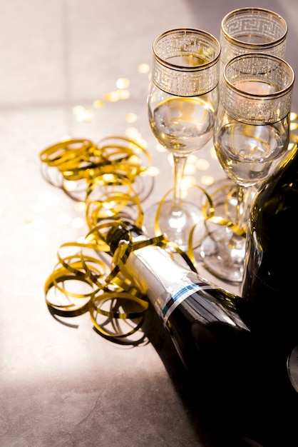 Close-up of empty champagne bottle and glass with golden streamers at party Free Photo