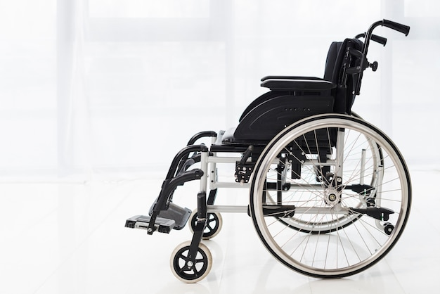 Close-up of an empty wheelchair in a room with white curtain Free Photo