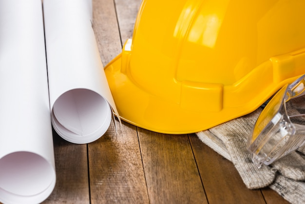 Close-up of engineer or foreman safety helmet and equipment on wooden table Premium Photo