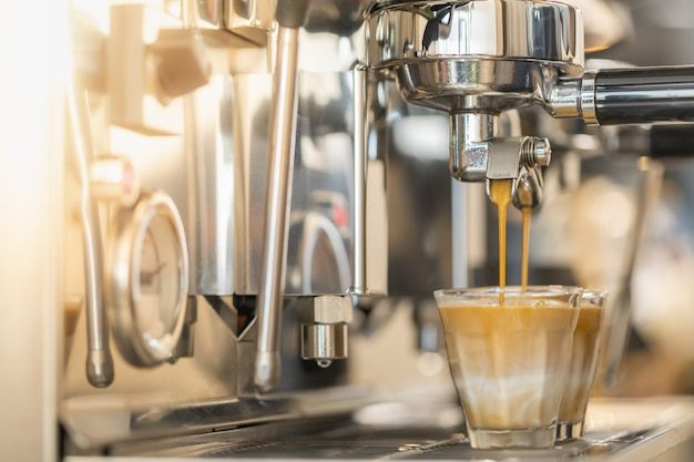 Close up of espresso pouring from automatic coffee machine Premium Photo