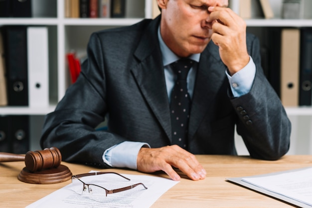 Close-up of exhausted male mature lawyer sitting in front of desk Free Photo