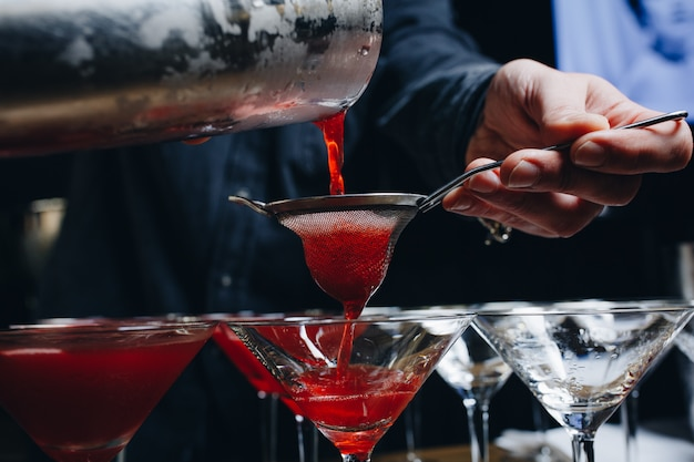 Close-up of expert bartender making red cocktail on the bar Premium Photo