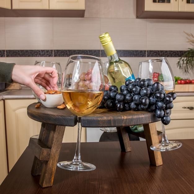ぼやけたキッチンのワイングラスホルダーの拡張可能な木製トレイを閉じます Premium写真