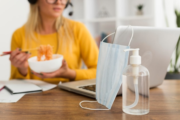 Close-up face mask and hand sanitizer on the desk Premium Photo