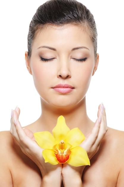 Крупным планом лицо красоты азиатской женщины релаксации с цветком в руках Бесплатные Фотографии