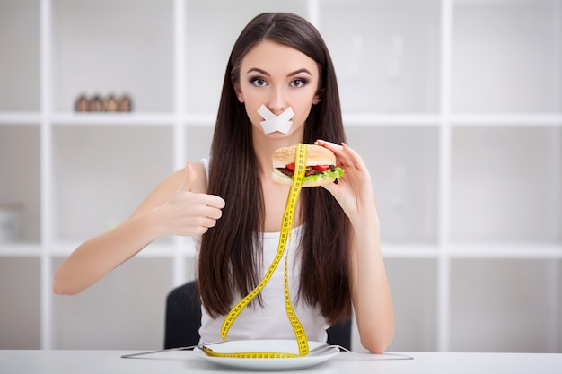 Close up face of young beautiful sad latin woman with mouth sealed on stick tape Premium Photo
